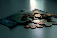 Geld nooit slaap Contant geld bij maanlicht, euro bankbiljetten en muntstukken op lijst Donker bedrijfsconcept royalty-vrije stock afbeeldingen