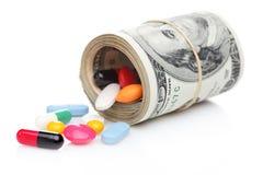 Geld oben gerollt mit den Pillen, die heraus fließen Stockfotografie