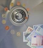 Geld onderaan het afvoerkanaal stock foto