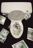 Geld onderaan het Toilet Stock Foto's