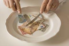 Geld op een plaat die als voedsel met een mes en een vork worden gesneden Stock Fotografie