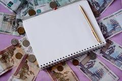 Geld Russische die roebels en rekeningen op een purpere achtergrond worden verspreid Blocnote en pen, begrotingsberekening royalty-vrije stock foto