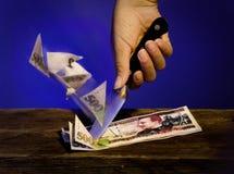 Geld schnitt eigenhändig mit Messer stockfotografie