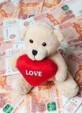 Geld Teddybär, der auf dem Geld sitzt Geld aus verschiedenen Ländern lizenzfreies stockbild