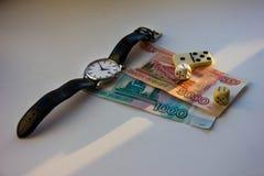 Geld, Uhr, Würfel und Domino Lichtstrahl fällt auf den Geldrubel, Würfel, Uhr, Domino Lizenzfreies Stockbild