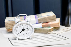 Geld, Uhrwecker und ein Ordner mit Dokumenten Lizenzfreie Stockfotos