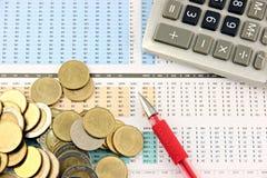 Geld und Büroeinrichtung, die auf Geschäftsdiagramm gesetzt wird. Stockbild