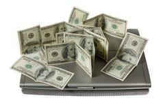 Geld und der Laptop Stockbilder