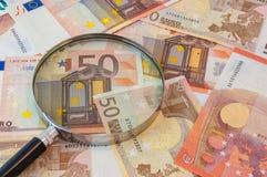Geld und ein Vergrößerungsglas Lizenzfreies Stockbild