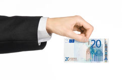 Geld und Geschäftsthema: übergeben Sie in einem schwarzen Anzug, der einen Euro der Banknote 20 lokalisiert auf einem weißen Hint Stockbilder