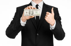 Geld und Geschäftsthema: ein Mann in einem schwarzen Anzug, der eine Rechnung von 100 Dollar hält und kennzeichnet ein Handzeiche Lizenzfreie Stockbilder