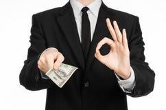 Geld und Geschäftsthema: ein Mann in einem schwarzen Anzug, der eine Rechnung von 100 Dollar hält und kennzeichnet ein Handzeiche Stockfotografie