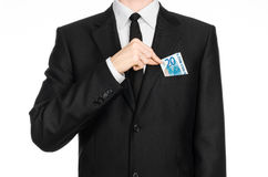 Geld und Geschäftsthema: ein Mann in einem schwarzen Anzug, der eine Rechnung von 20 Euros und von Shows ein Handzeichen auf eine Stockbilder