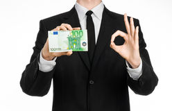 Geld und Geschäftsthema: ein Mann in einem schwarzen Anzug, der eine Rechnung von 100 Euros und von Shows ein Handzeichen auf ein Lizenzfreie Stockfotografie