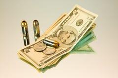 Geld und Gewehrkugeln Lizenzfreies Stockfoto