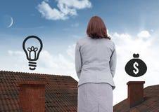 Geld und Glühlampe Ikonen und Geschäftsfrau, die auf Dächern mit Kamin und und blauem Himmel stehen Stockfotos