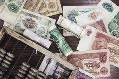 Geld und hölzerner Abakus Stockfoto