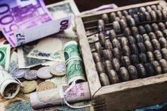 Geld und hölzerner Abakus Stockfotos