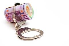 Geld und Handschellen Stockfoto