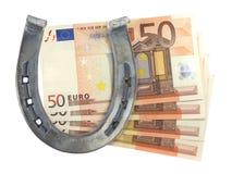 Geld und Hufeisen Lizenzfreie Stockfotos