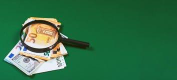 Geld und Lupe auf grünem Hintergrund lizenzfreie stockbilder