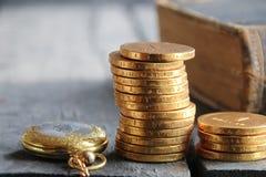 Geld und Prozentsatzsymbol in den Händen Stapel der goldenen Münzen Stockfotos