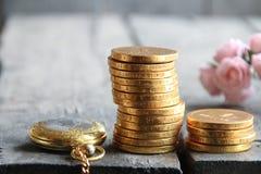 Geld und Prozentsatzsymbol in den Händen Stapel der goldenen Münzen und der Blumen Lizenzfreie Stockbilder