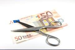 Geld und Scheren Stockfoto