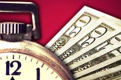 Geld-und Silber-Taschen-Uhr auf rotem Hintergrund Lizenzfreie Stockfotos