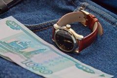 Geld und Stunden auf den Jeans Lizenzfreie Stockbilder