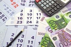 Geld und Taschenrechner auf Monatskalender Stockbilder