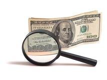 Geld und Vergrößerungsglas stockbild