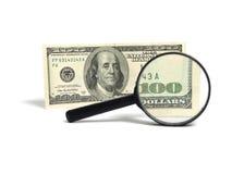Geld und Vergrößerungsglas Stockfotografie