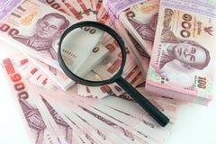 Geld und Vergrößerungsglas lizenzfreie stockfotos