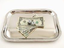 Geld und Würfel auf einem silbernen Tellersegment Stockfotos