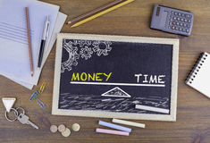 Geld und Zeit-Balance Tafel auf hölzernem Schreibtisch Stockbilder