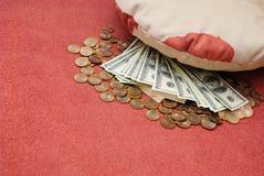 Geld unter einem Kissen Lizenzfreie Stockbilder