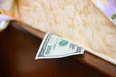 Geld unter einer Matratze Stockbild