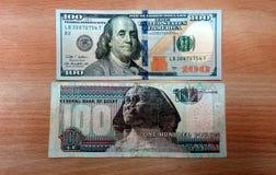 Geld 100 USD versus 100 EGP Stock Afbeelding