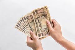 Geld van de onderneemsterholding10,000 het Japanse Yen ter beschikking op witte achtergrond, Japanse Yen in financieel concept in Stock Foto