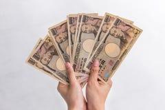 Geld van de onderneemsterholding10,000 het Japanse Yen ter beschikking op witte achtergrond, Japanse Yen in financieel concept in Stock Afbeeldingen