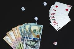 Geld, würfelt und kardiert auf einem schwarzen Hintergrund Nahaufnahme stockbild