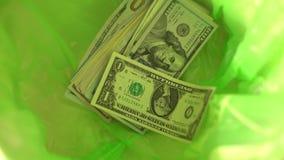 Geld wegwerfend, fallen Dollar in grünen Abfalleimerkorb, Freiheit von der Finanzierung und vergeuden Geld stock footage
