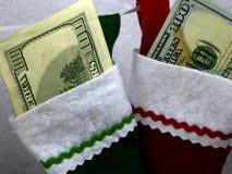 Geld-Weihnachtsstrümpfe lizenzfreie stockbilder