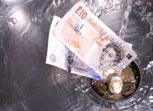 Geld wusch unten den Ablaß Stockfoto