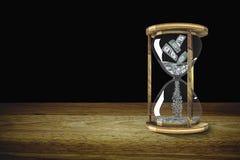 Geld in zandloper De tijd is kostbaar concept Afmeting drie Royalty-vrije Stock Afbeeldingen
