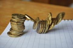 Geldachtergrond van dalende stapel van muntstukken als symbool van financiële verslechtering stock afbeelding