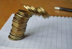 Geldachtergrond van dalende stapel van muntstukken als symbool van financiële verslechtering stock fotografie