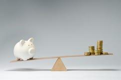 Geldausgaben gegen Geldeinsparungen Stockfoto