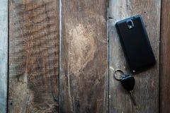 Geldbörse, Autoschlüssel und Mobile auf einem Bretterboden lizenzfreies stockbild